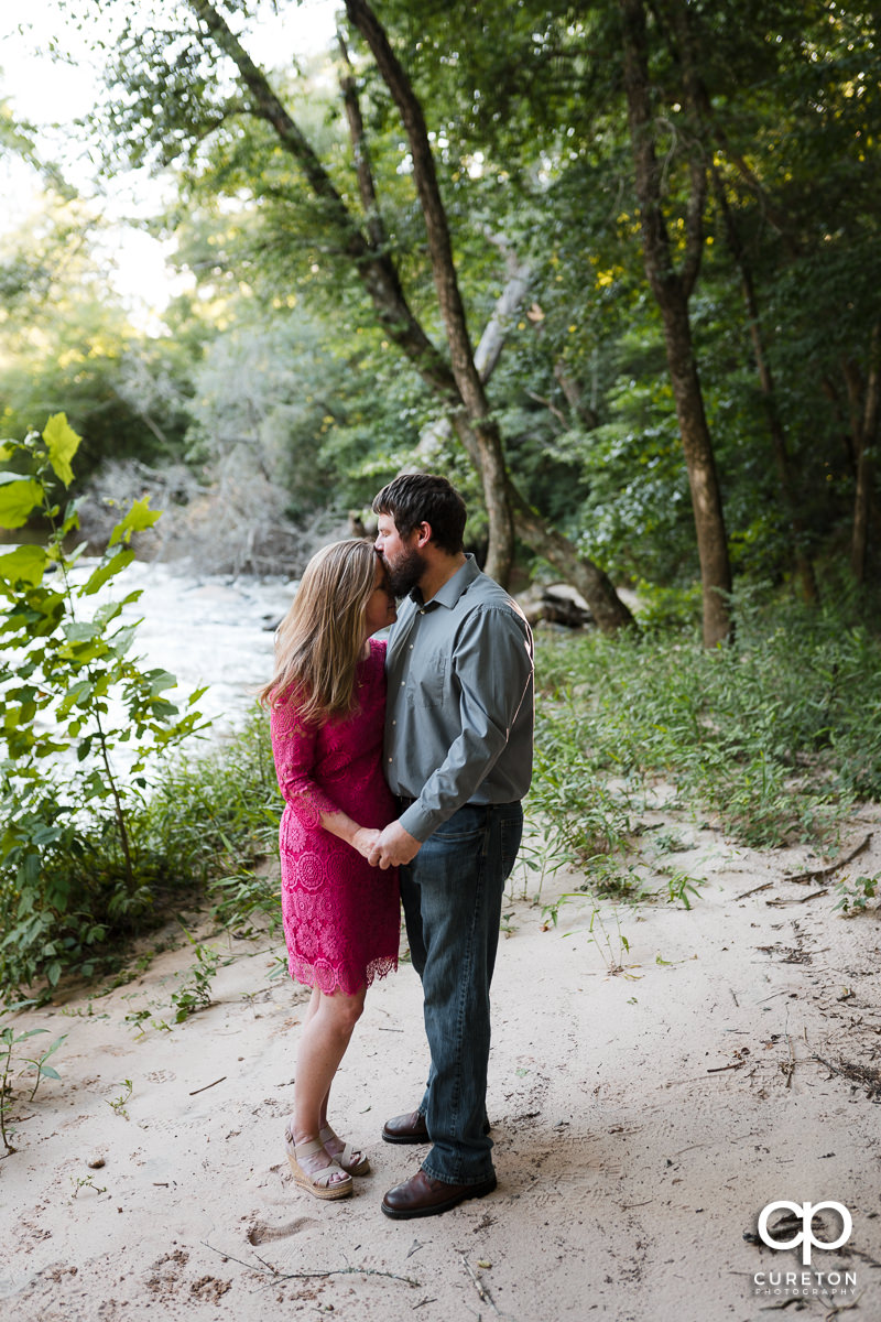 Man kissing his future brode on the forehead on the banks of a river during a summer engagement session in Greer,SC.