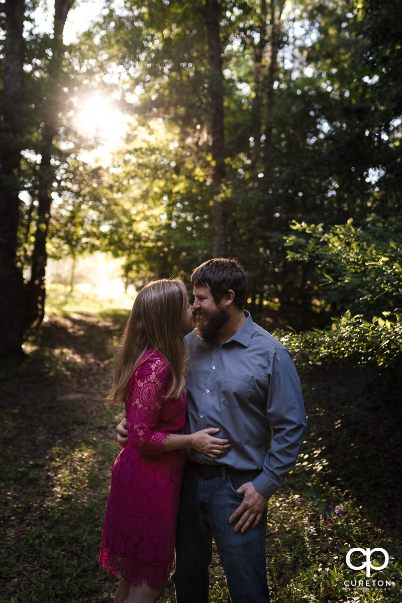 Man and his future wife dancing in the forest during a summer engagement session in Greer,SC.