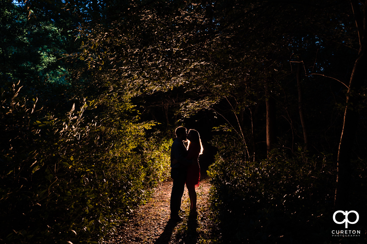 Engaged couple kissing in the forest at night.