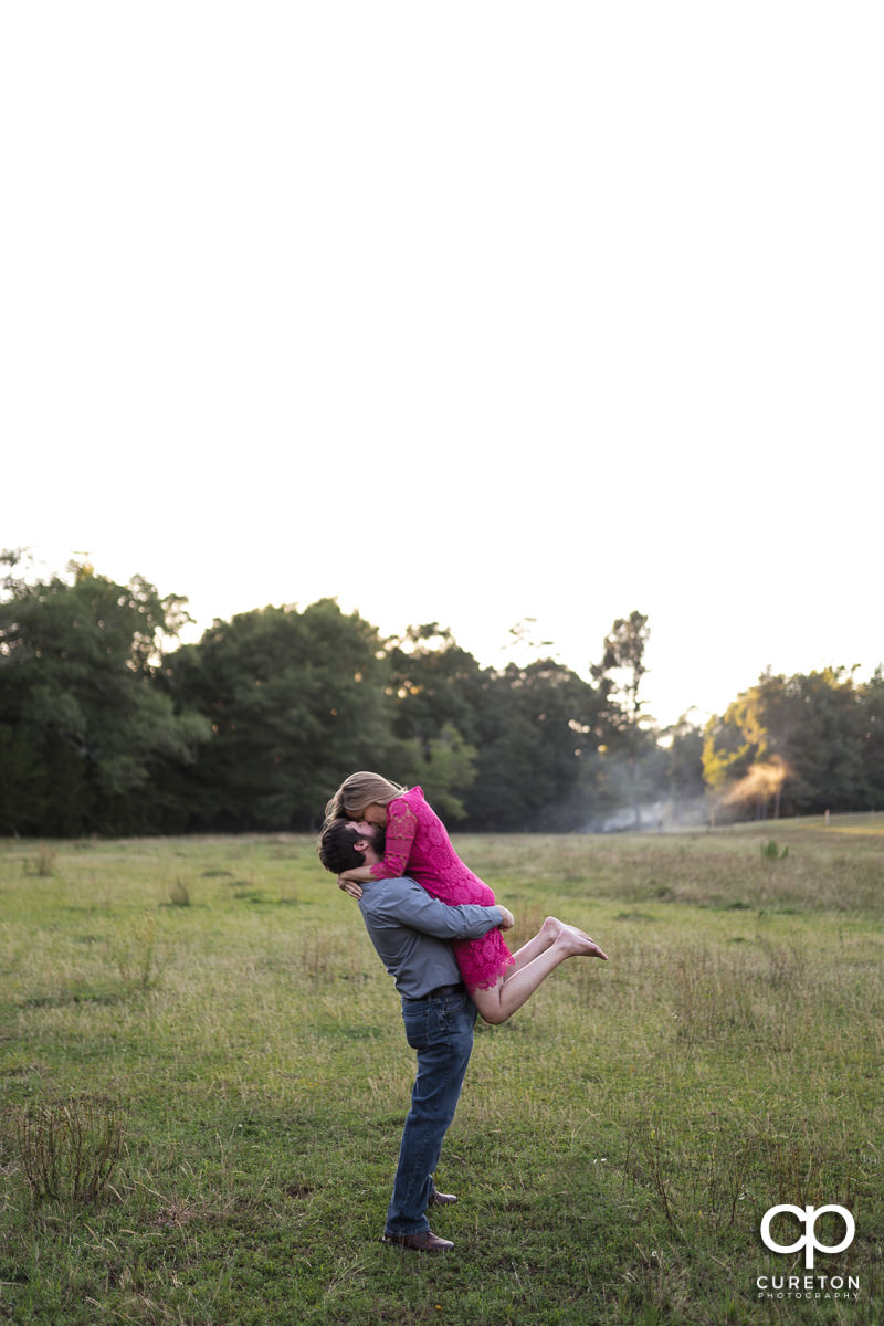 Man lifting his future bride into the air during a summer engagement session in Greer,SC.
