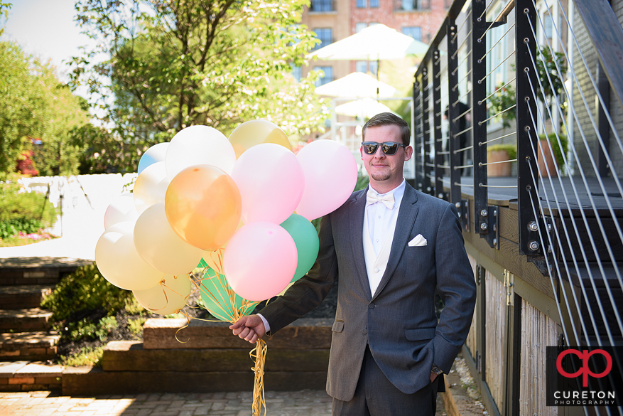 Groom awaits first look with balloons in his hand.
