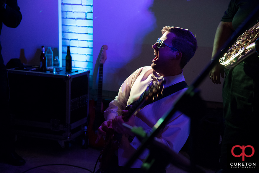 Groom plays guitar with the wedding band.