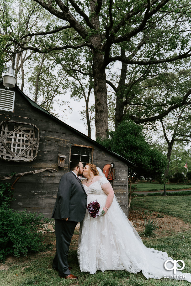 Bride and groom kissing in front of a barn at their Grove at Pennington wedding in Greer,SC.