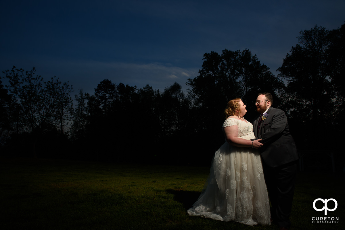 Bride and groom smiling at each other at sunset after their Grove at Pennington wedding in Greer,SC.