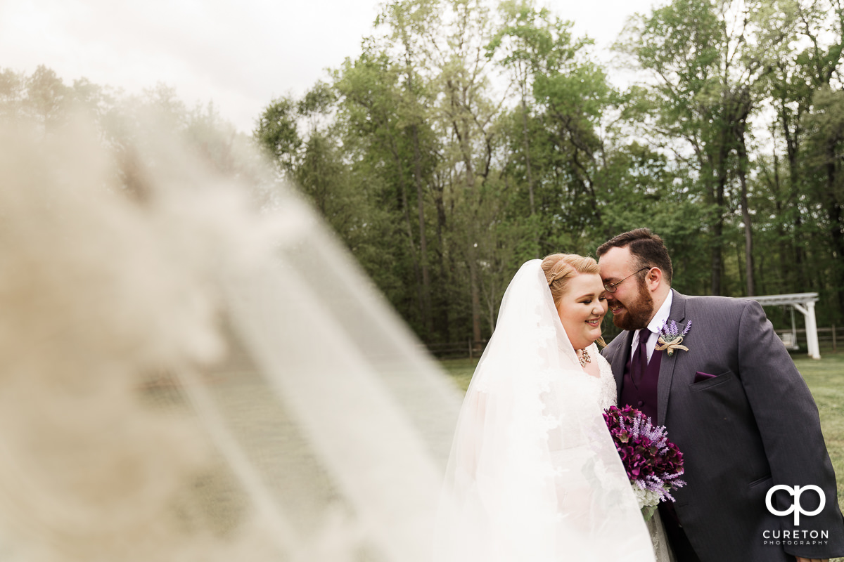 Groom snuggling his bride as her veil blows into the wind at their Grove at Pennington wedding in Greer,SC.