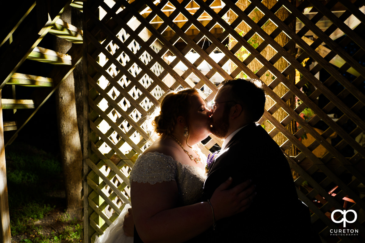 Bride and groom backlit in front of a lattice wall at their Grove at Pennington wedding in Greer,SC.