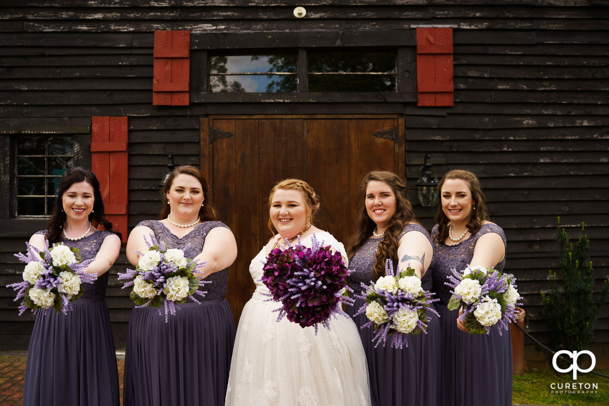 Bride and bridesmaids holding out their flowers.