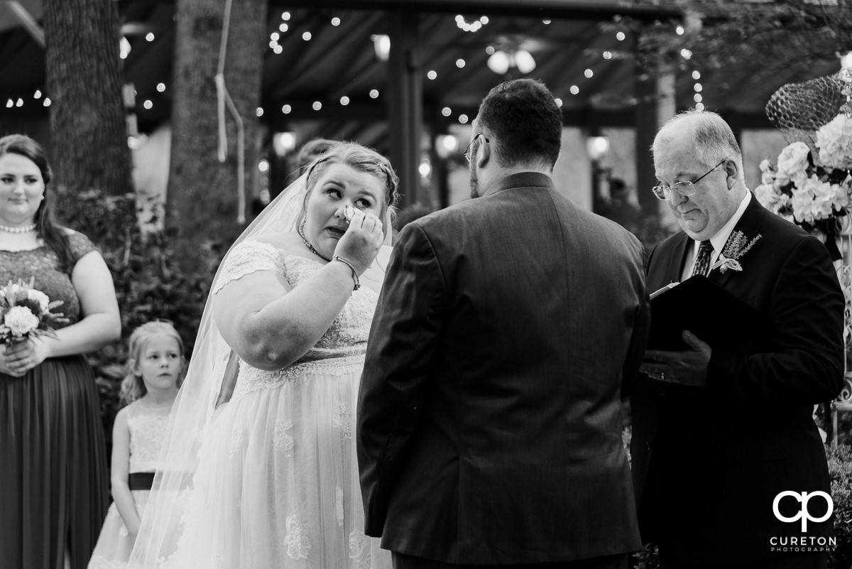Bride wiping tears at the ceremony.
