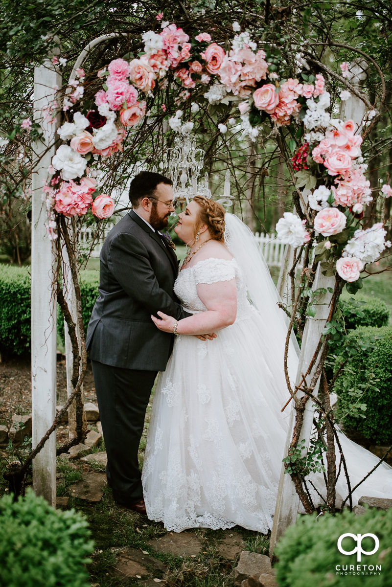 Bride and groom underneath a floral arch at the wedding.