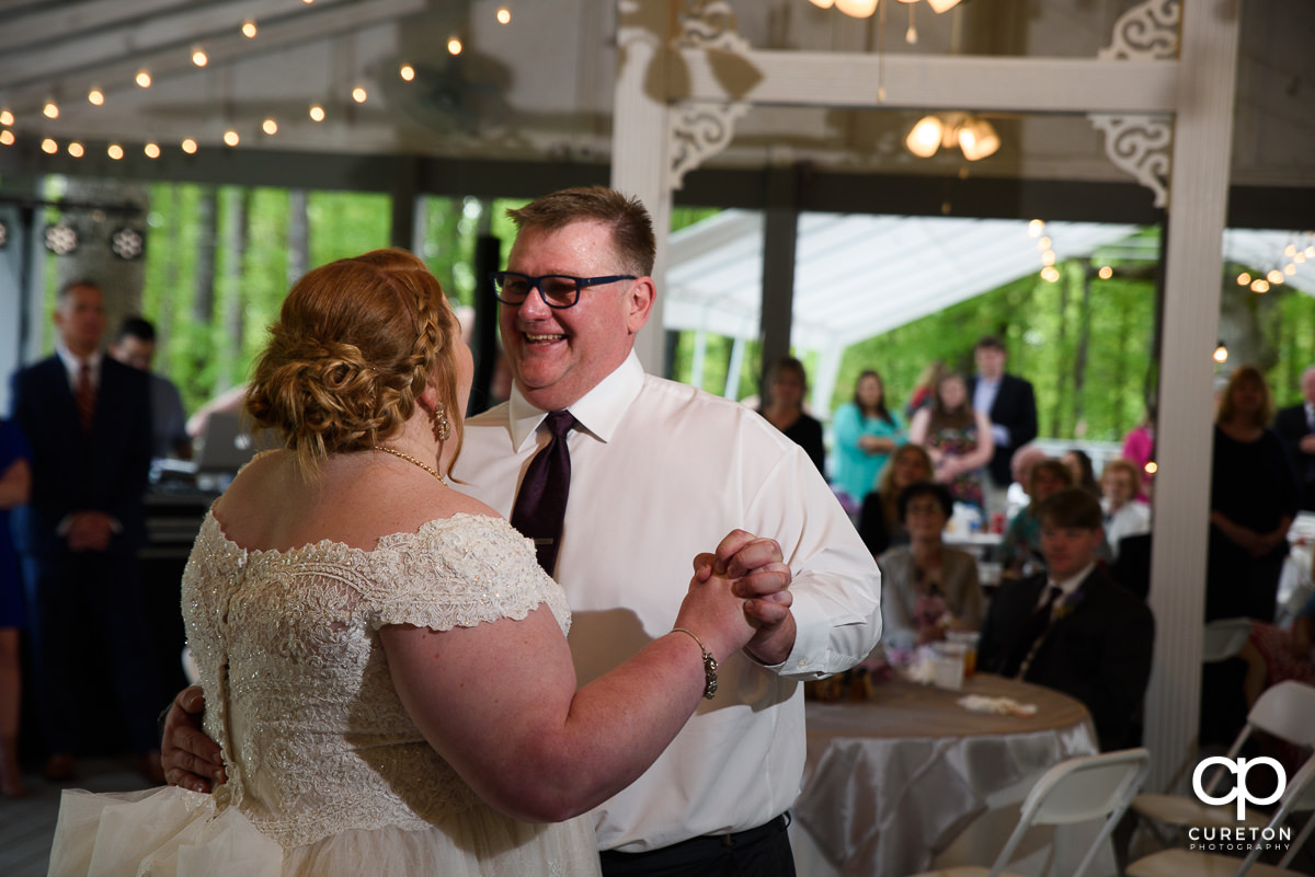 Bride's dad smiling during their first dance.