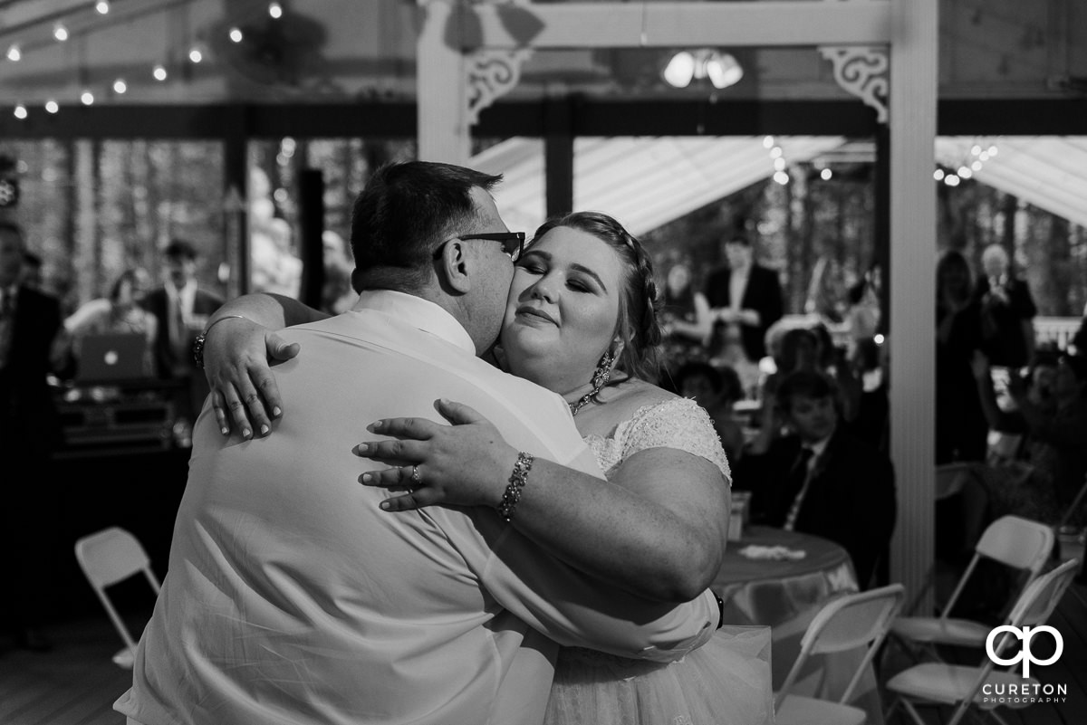 Bride's father kissing her on the cheek after a dance at the reception.