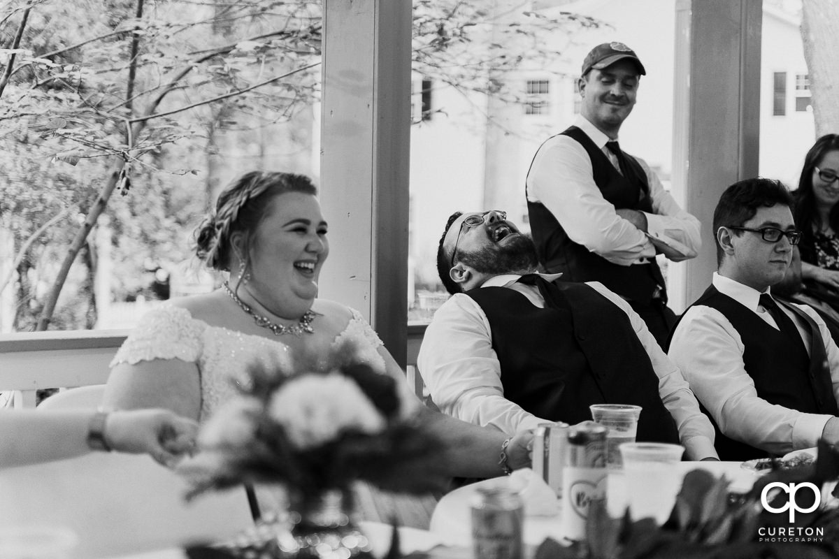 Bride and groom laughing a a speech at the reception.