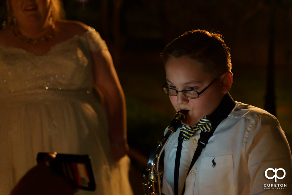 Kid at the wedding playing a saxophone.