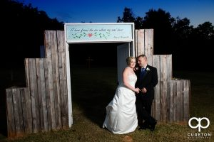 Bride and groom posing by the doors outside the hollow at Paris mountain.