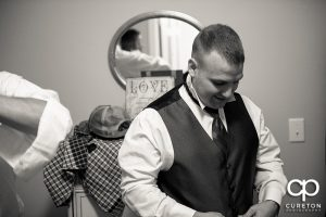 The groom putting his tux on.