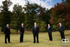 The groomsmen standing in a field.