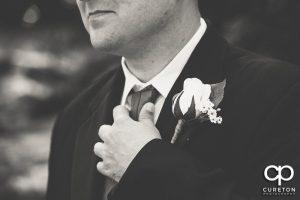 The groom adjusting his tie.