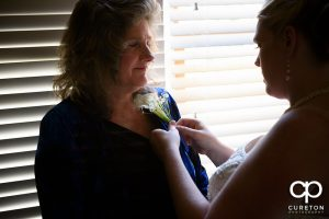 The bride pinning a flower on her mother.