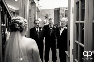 Bride having a first look with her dads.