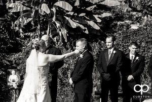 Bride wiping a tear from the groom's eye.