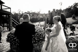 Bride and groom tying a knot in a rope during their wedding ceremony.