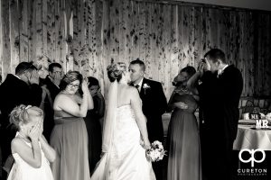 Bride and groom kissing at the reception.