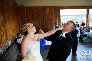 Bride and groom smashing cake.