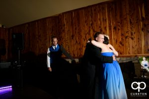 Maid of honor hugging the bride and groom