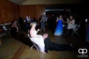 Groom dancing as he takes the garter off.
