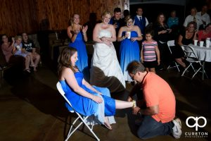 Man who caught the garter putting it back on the woman who caught the bouquet.