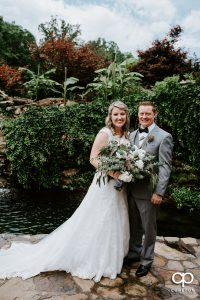 Bride and groom standing near a pond at The Hollow at Paris Mountain.