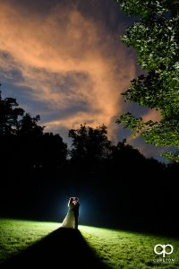 Bride and groom kissing underneath an amazing sunset after their wedding at The Hollow at Paris Mountain.