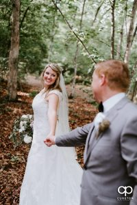 Bride and groom running through the woods at their Hollow at Paris Mountain wedding.