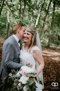 Bride laughing at her groom in rhe woods.