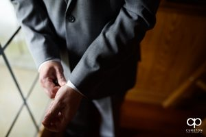 Groom fixing his cuffs.