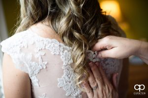 Bride's mom buttoning the back of her dress.