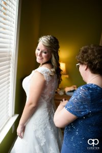 Bride looking back at her mother helping her with her dress.