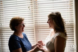 Bride and her mother having a moment in the window before the wedding ceremony at The Hollow at Paris Mountain