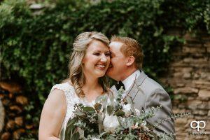 Groom whispering in his bride;s ear.