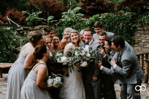 Wedding party hugging the couple before the ceremony at The Hollow at Paris Mountain.