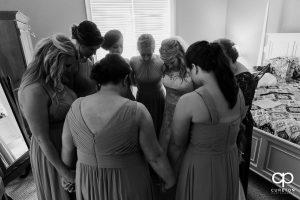 Bride praying with her bridesmaids.