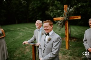 Groom smiling as he sees his bride walking down the aisle for the first time.