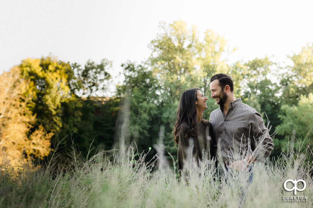 Man and his fiancee standing in some tall grass during a Greenville SC Falls Park Engagement Session.