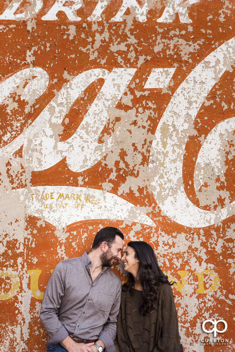 Man and his fiancee standing in front of a painted Coca-Cola wall in downtown Greenville,SC.