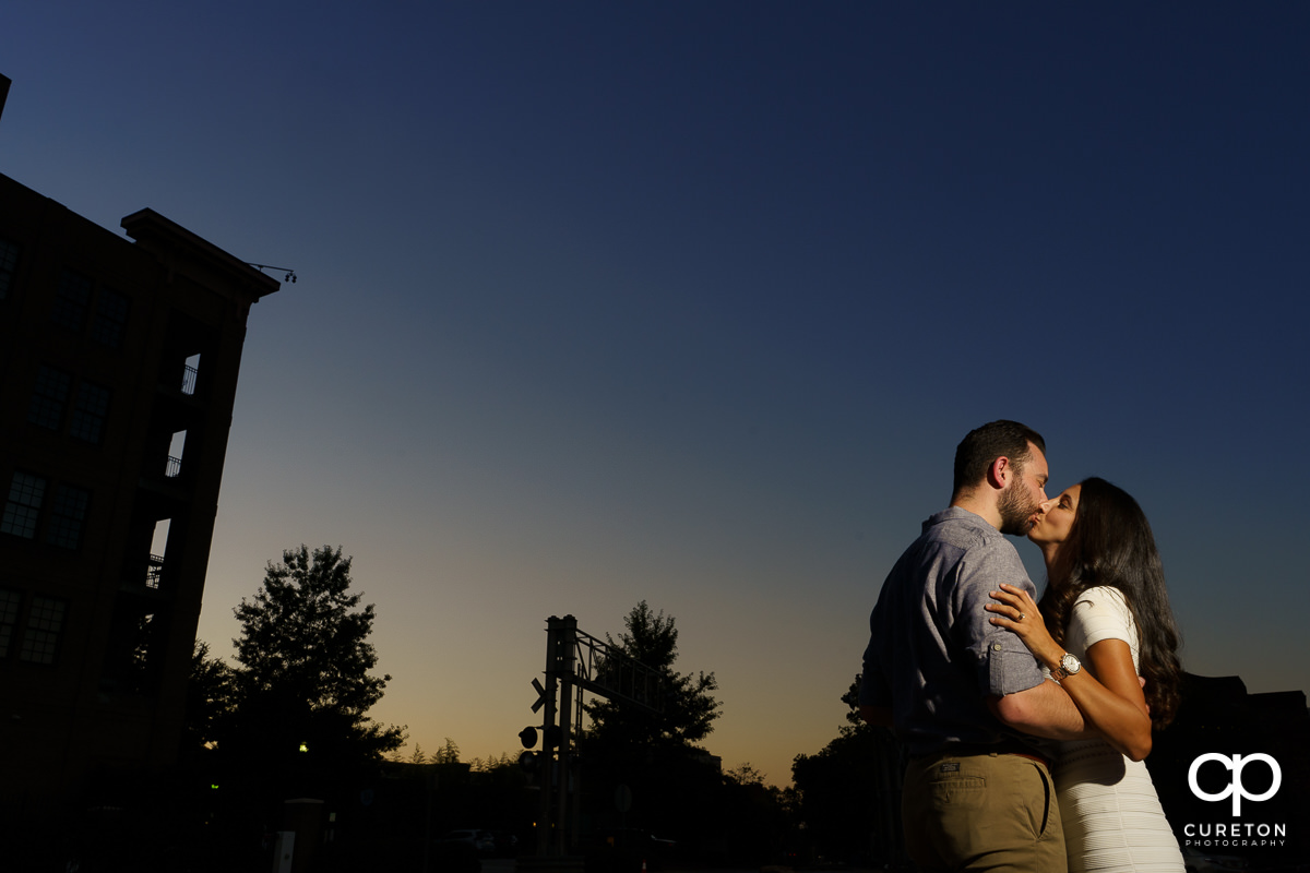 Man kissing his fiancee during sunset at their engagement session in Greenville,SC.