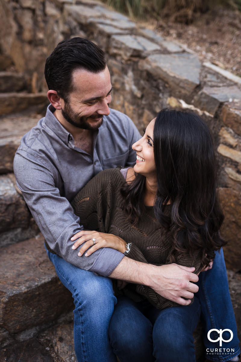 Engaged couple sitting in some steps at Falls Park in downtown Greenville,SC.