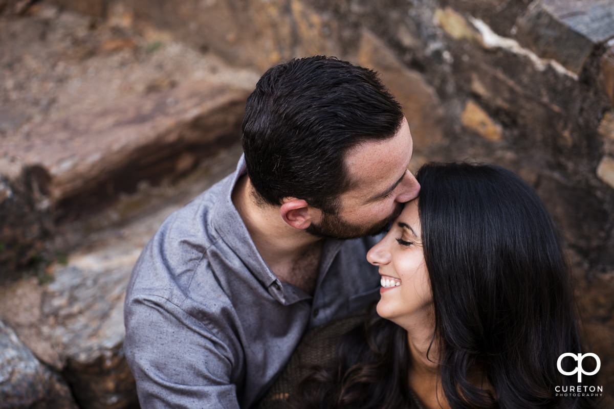 Man kissing his fiancee on the forehead as she smiles.