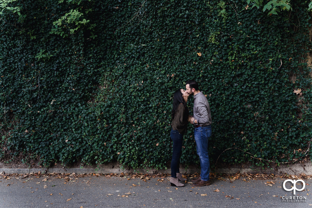 Man and his fiancee kissing in front of an ivy covered wall during their engagement session at Falls Park in downtown Greenville,SC.