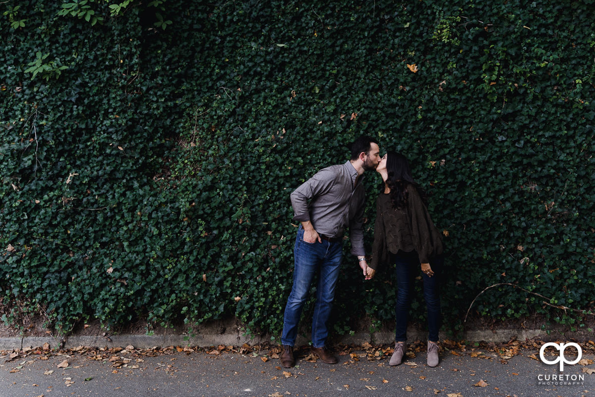Engaged couple stopping for a kiss in front of an ivy covered wall in downtown Greenville.