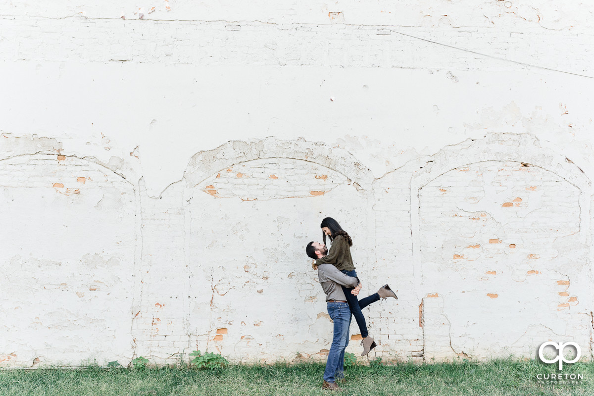 Man lifting his fiancee in front of a disheveled wall in Greenville,SC.
